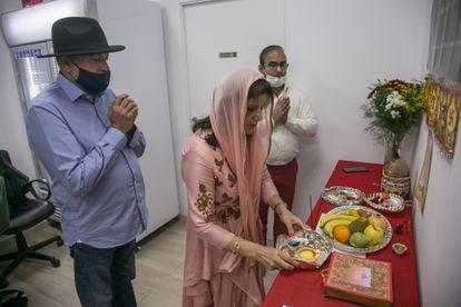 La familia Lalwani, durante el rezo de Diwali en la tienda Desi Gourmet, este sábado.