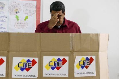 El presidente de Venezuela, Nicolás Maduro, se persigna mientras ejerce su voto en las últimas presidenciales, en Caracas el 20 de mayo de 2018.