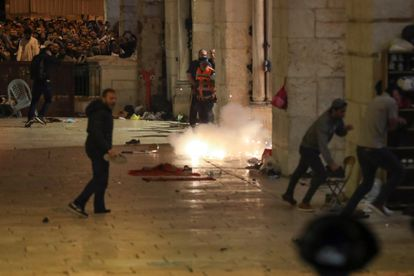 Israeli police throw stun grenades to evict Palestinian worshipers from Al Aqsa Mosque in Jerusalem on Friday.