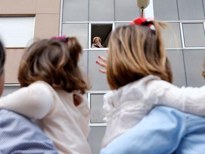 Una abuela saluda a sus nietas desde la ventana de su casa en La Palma, este domingo.