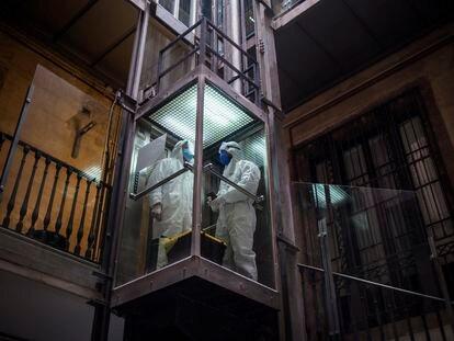 Imagen de 'Covid Photo Diaries' en la que sanitario y un trabajador de Open Arms suben a un domicilio de Barcelona, para realizar un test a una persona.