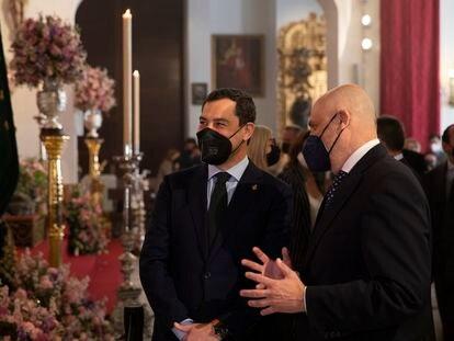 El presidente de la Junta de Andalucía, Juanma Moreno (izquierda), junto a el Hermano Mayor de la Hermandad de Triana, Sergio Sopeña Carriazo (derecha), durante la visita a la Capilla de los Marineros. Sevilla (Andalucía, España), a 29 de marzo 2021.