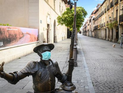 Estatua de Don Quijote con una mascarilla frente a la Casa Natal de Miguel de Cervantes en Alcalá de Henares.