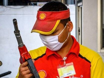 Un empleado de una gasolinera Shell en Bangkok, pertrechado con una mascarilla para protegerse del coronavirus.