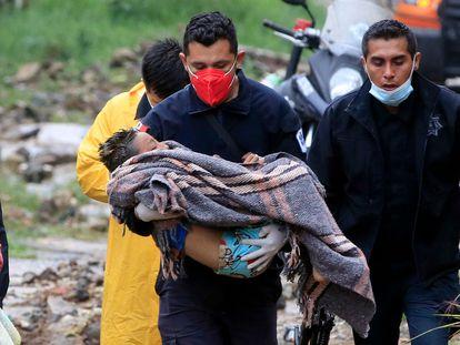Un paramédico de seguridad pública lleva a un niño luego de que un deslizamiento de tierra de una colina aplastara una casa debido al paso del huracán 'Grace', en el barrio Loma Bonita en Xalapa.