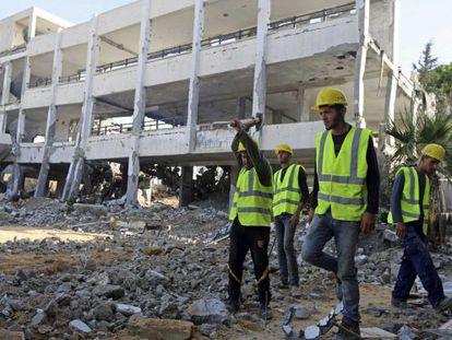 Trabajadores palestinos limpian esgombros de una escuela de la UNRWA, en Gaza, destruida durante el reciente conflicto entre Israel y Hamás.