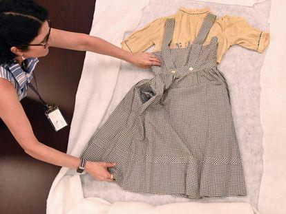 Maria Mazzenga, una de las responsables de conservación de la Universidad Católica de Washington, manipula el vestido de Judy Garland como Dorothy en 'El mago de Oz', en una imagen divulgada por el centro educativo.