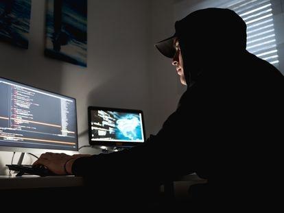 Un hombre, frente a las dos pantallas de su ordenador.