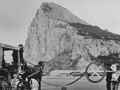 Tráfico en la carretera que lleva de España a Gibraltar, esperando en la barrera a que aterrice un avión, en una imagen de la primera mitad del siglo XX.
