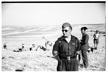 Un oficial del Ejército franquista posa delante de unos prisioneros republicanos que cavan una trinchera en Brunete.