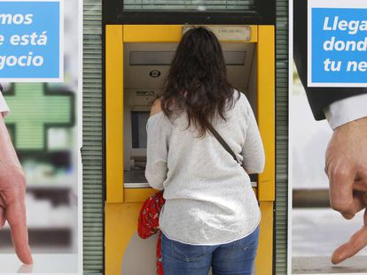 Una joven utiliza un cajero automático en una oficina bancaria, en Madrid.