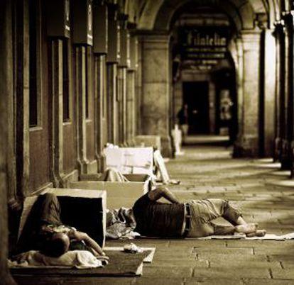 Varias personas durmiendo en los soportales de la plaza Mayor.