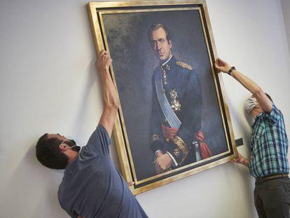 <b>Juan Carlos I, descolgado.</b> Dos operarios retiran el retrato del rey emérito Juan Carlos I de la Sala de Gobierno del Legislativo foral del Parlamento de Navarra, el pasado 15 de junio.