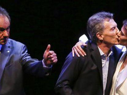 Macri recibe el beso de su esposa mientras Scioli saluda al público tras el debate electoral del pasado 18 de noviembre.