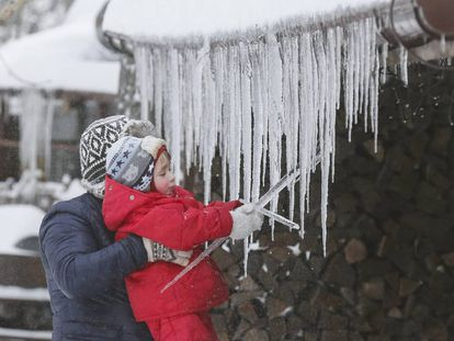 Una niña juega con unas estalactitas de hielo.