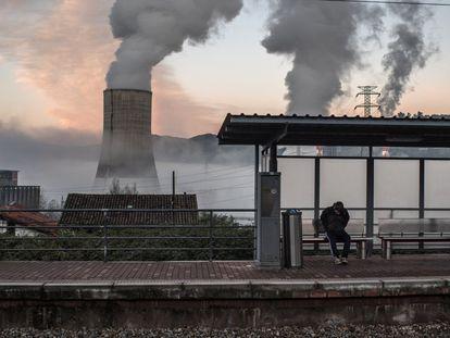 Las regiones carboníferas de España, situadas principalmente en Asturias y León, se enfrentan a un futuro incierto. En la imagen, un trabajador espera en la estación de tren de Las Segadas, con la central de energía térmica de Soto de Ribera de fondo, en Entrepuentes (Asturias),