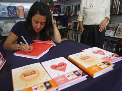 La autora del libro autoeditado 'Cree en ti', Rut Nieves, firma uno de sus ejemplares en la Feria del Libro de Madrid.