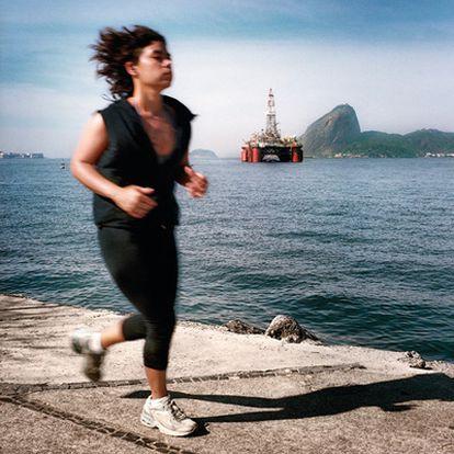 Bahía de Niteroi, a las afueras de Río. Una mujer corre delante de una plataforma petrolífera y el cerro del Pan de Azúcar.
