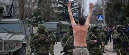 Un hombre ucranio protesta frente a soldados sin identificar y que hacen guardia en Balaklava, a las afueras de Sebastopol, en Ucrania.