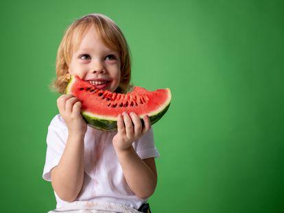 Un niño come sandía.