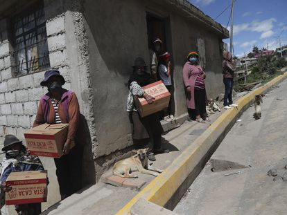 Vecinas de las afueras de Quito reciben las cajas de alimentos repartidas por el Gobierno durante la cuarentena.