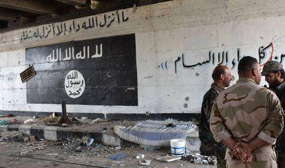 Militares sirios al lado de un grafiti pintado por el Estado Islámico en Alepo, la semana pasada.