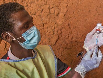 Un médico de una unidad móvil coloca la vacuna en una jeringuilla para administrarla a un niño en un asentamiento en Toro, Nigeria, en octubre de 2020.