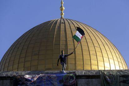 Un hombre ondea la bandera de Palestina en Al Aqsa, Jerusalén, durante las celebraciones del Eid al-Fitr, este jueves.