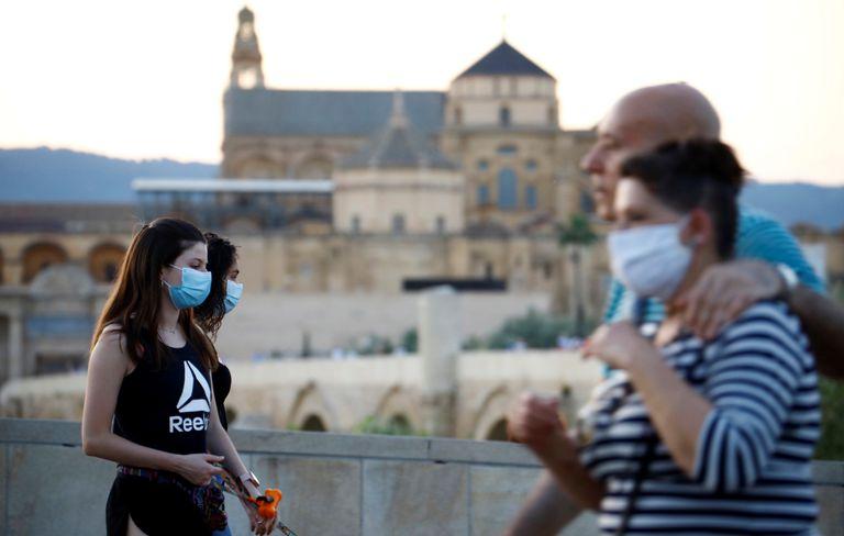 Ciudadanos protegidos con mascarillas pasean por las inmediaciones de la Mezquita y la Catedral de Córdoba.