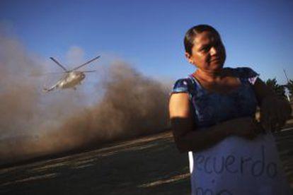 Una mujer con un cartel que apoya a El Americano se retira del sitio donde despega el helicóptero militar que transporta al expolicía rural detenido.