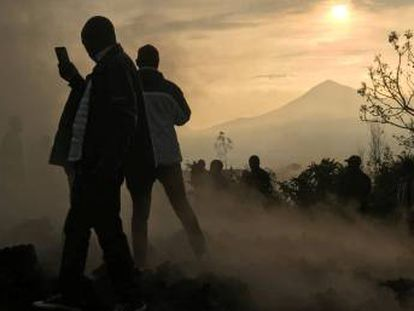 Un hombre usa su teléfono móvil para tomar fotografías de casas destruidas por la lava, que aún sigue humeante, cerca de Goma (República del Congo), este domingo.