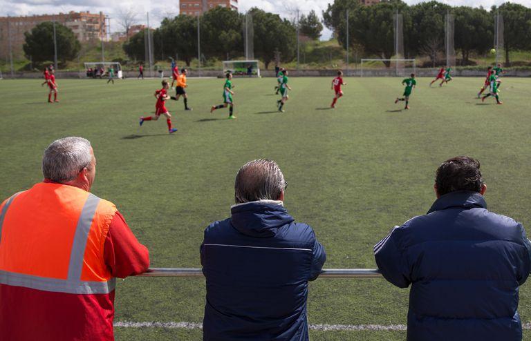 Varios padres observan desde la banda un partido infantil, en un campo de Parla (Madrid). Alfredo Di Stefano en Parla Foto: Víctor Sainz