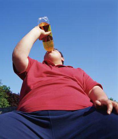 Un hombre obeso bebe de una botella.