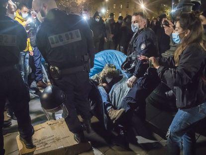 Un agente evacúa a un inmigrante junto a su tienda, durante la madrugada del martes en la Plaza de la República de París.