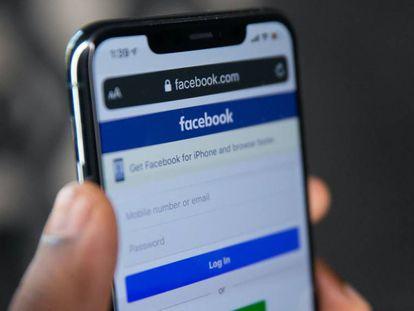 Un usuario de Facebook sostiene un teléfono móvil.