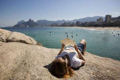 El estudiante Victor Caplin lee un libro en las piedas del Arpoador, en la playa de Ipanema.