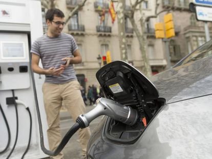 Un usuario de coche eléctrico recarga las baterías de su vehículo en Barcelona.