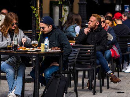 Personas sentadas en febrero en la terraza de un bar en la plaza de Santa Ana, en Madrid.