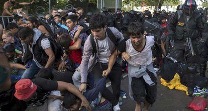 La policía empuja a migrantes en la frontera húngara hoy.