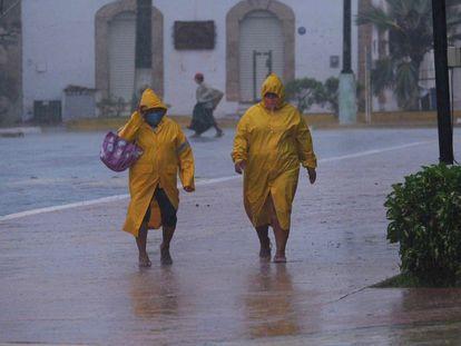 Dos personas caminan en medio de la tormenta en el poblado de Tizimin, Yucatán.