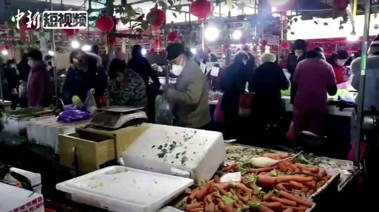 Compradores portan mascarillas en un mercado de la ciudad de Wuhan, en China.