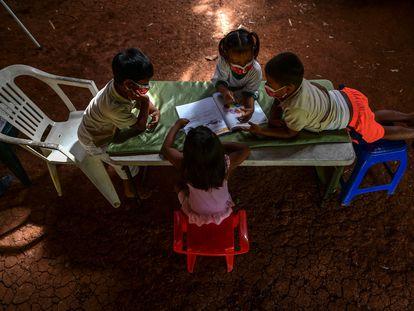 Niños indígenas emberá consultan un libro durante las clases en su comunidad en marzo de 2021, en Panamá.