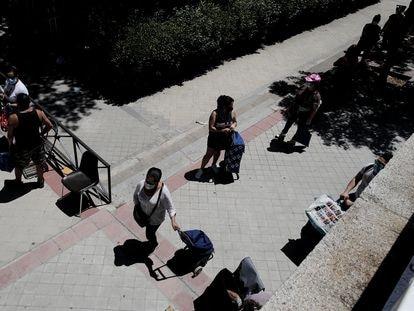 Colas de personas esperan a las puertas de la Parroquia Santa María Micaela de Madrid para recibir ayuda alimentaria.