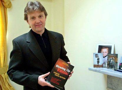 Alexander Litvinenko, en su casa de Londres, muestra un libro suyo sobre el espionaje ruso.