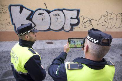 Agentes de la policía local de Málaga realizan fotos a uno de los grafitis aparecidos en una de las calles de la ciudad.