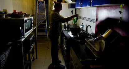 Una mujer en la cocina de su vivienda afectada por los cortes de luz y agua.