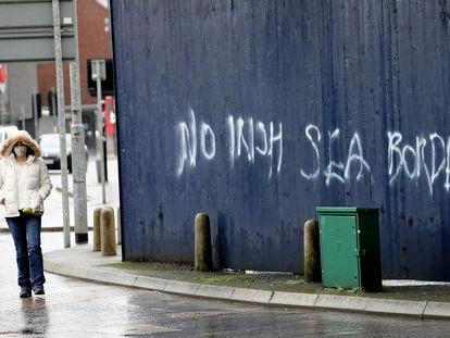 Una mujer camina el 3 de febrero a lado de una de las pintadas contra la frontera del mar de Irlanda, en Belfast.