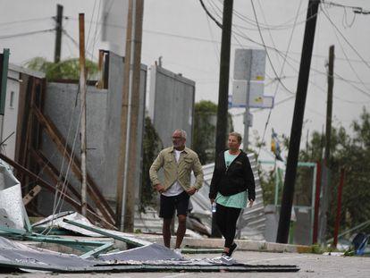 Turistas caminan entre los escombros que cubren la calle después de la llegada del huracán Zeta a Playa del Carmen, México