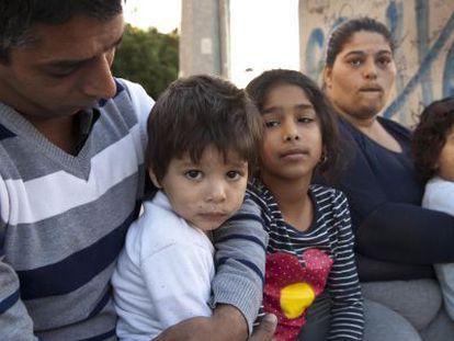 Juana Amador con sus hijos y su marido ante el polideportivo Ciudad Jardín de Alicante en el que se encuentran alojados.