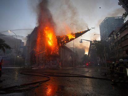 Un hombre fotografía el momento en que se derrumba el campanario en llamas de la Iglesia de la Asunción, el domingo 18 de octubre en Santiago de Chile